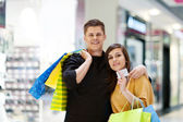 Young couple with shopping bags — Stock Photo