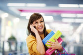 Beautiful woman on the phone in shopping mall — Stock Photo