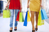 Low section of young friends carrying shopping bags — Stock Photo