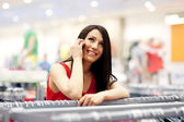 Smiling young woman on the phone at shopping mall — Stock Photo