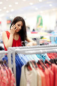 Attractive young woman on the phone at shopping — Stock Photo
