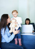 Mother entertaining her daughter at doctors office — Stock Photo