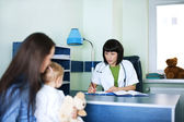 Mother and baby girl at the doctors office — Stock Photo