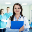 Portrait of young female doctor with interns in background — Stock Photo