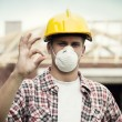 Manual worker with hard hat and protective mask - Stock Photo