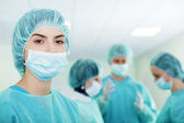 Young female surgeon with medical team in back before surger — Photo