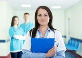 Retrato do jovem médico feminino com internos no fundo — Foto Stock