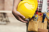 Close-up of hard hat holding by construction worker — Stok fotoğraf