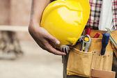 Gros plan d'un casque, tenant par travailleur de la construction — Photo