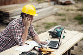 Carpenter talking on mobile phone — Stock Photo