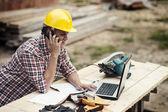 Carpenter talking on mobile phone — Stock Photo