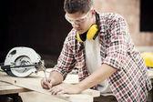 Carpenter measuring a wooden plan — Stock Photo