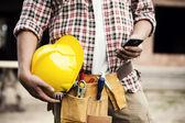Primer plano de construcción trabajador mensajes de texto en el teléfono móvil — Foto de Stock