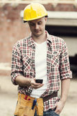 Construction worker texting on mobile phone — Stock Photo