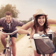 Happy couple racing on bikes - Stock Photo