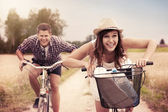 Happy couple racing on bikes — Photo