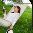 Relaxing in hammock with drink - Stock Photo