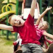Two kids slide on playground - Stock Photo