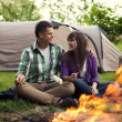 Couple near a campfire  toasting marshmallow - Stock Photo