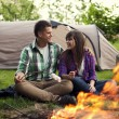 Couple near campfire toasting marshmallow — Stock Photo #21907823