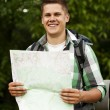 Man holding a map in forest — Stock Photo