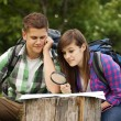 Young couple with map in forest — Stock Photo