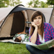 Young woman sitting near tent — Stock Photo