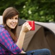 Young womsitting near tent — Stock Photo #21908487
