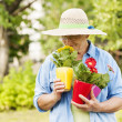 Senior woman smelling flowers — Stock Photo #21909059
