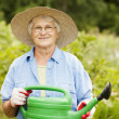 Woman holding watering can - Stock Photo