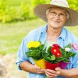 Senior woman with flowers in garde — Foto Stock