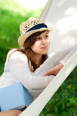 Woman relaxing in a hammock with book — Stock Photo