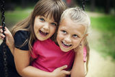 Happy little girls swinging in a park — Stock Photo