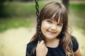 Portrait of smiling girl on swing — Stock Photo