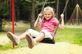 Happy girl swinging on playground — Stock Photo