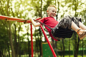 Cute boy swinging in a park — Stock Photo
