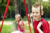 Children swinging together — Stock Photo