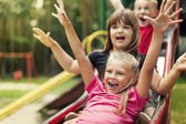 Happy kids playing on slide — Stockfoto
