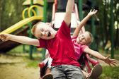 двое детей слайд на площадке — Стоковое фото