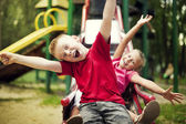Two kids slide on playground — ストック写真