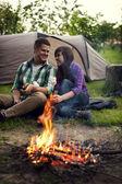 Couple near a campfire toasting marshmallow — Stock Photo