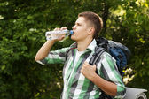 Hiker drinking water in forest — Stock Photo