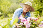 Senior woman with flowers — Stock Photo