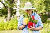 Senior woman smelling flowers — Stock Photo