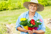 Senior woman with flowers in garde — Stockfoto