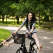 Happy young woman cycling through the park — Stock Photo