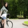 Woman with bicycle in park — Stock Photo #21910281