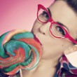 Stock Photo: Pin up girl eating lollipop