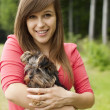 Smiling woman holding cute puppy — Stock Photo