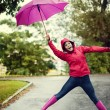 Young woman under pink umbrella — Stock Photo #21915577